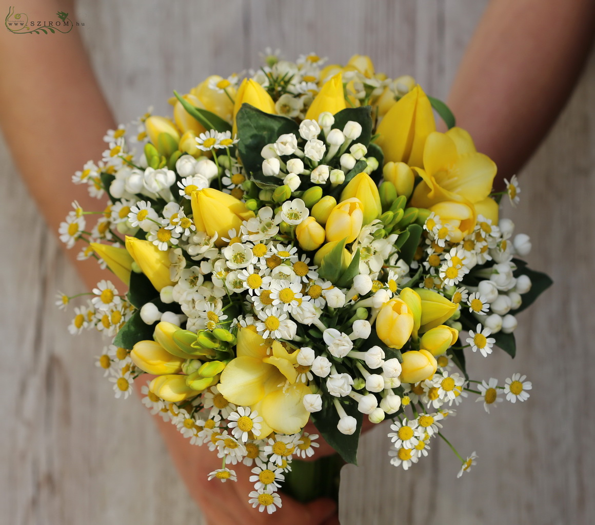 Bridal bouquet with yellow freesias, chamomilles, bouvardias and tulips